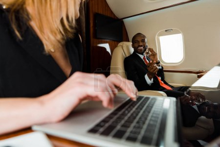 Photo for Selective focus of african american businessman gesturing near businesswoman using laptop in private plane - Royalty Free Image