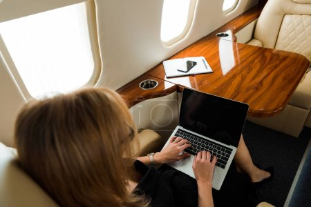 Photo for Overhead view of businesswoman using laptop with blank screen in private jet - Royalty Free Image