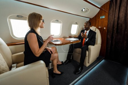 Foto de Feliz mujer de negocios en gafas apuntando con el dedo cerca de hombre de negocios afroamericano en avión privado - Imagen libre de derechos