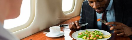 panoramic shot of african american businessman near tasty dish and businesswoman in private plane