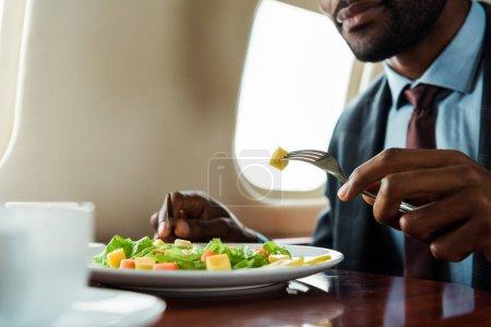 Photo pour Vue recadrée de l'homme afro-américain mangeant de la salade en avion privé - image libre de droit