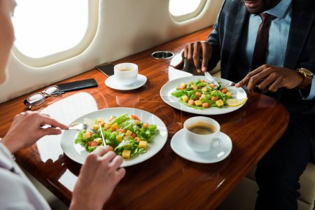 Photo for Cropped view of african american businessman near tasty dishes and businesswoman in private plane - Royalty Free Image