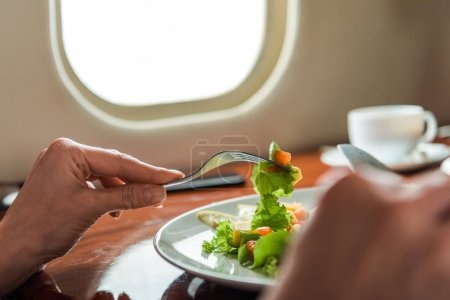 Photo pour Cropped view of woman holding cutlery near tasty salad in private jet - image libre de droit