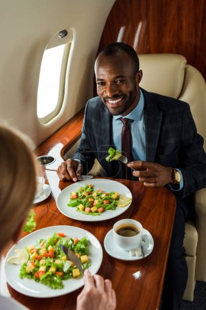 selective focus of happy african american businessman near delicious salads and woman in private plane