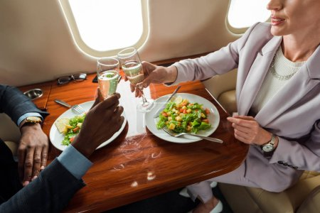 Photo pour Cropped view of businesswoman and african american businessman clinking champagne glasses in private jet - image libre de droit