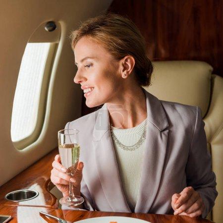 Foto de Alegre mujer de negocios con copa de champán en jet privado - Imagen libre de derechos