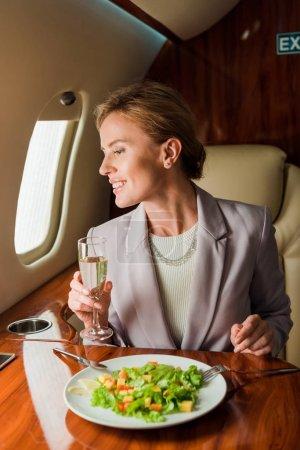 Glückliche Geschäftsfrau mit Champagnerglas neben leckerem Salat im Privatjet