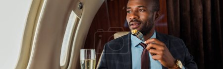 Photo pour Panoramic shot of africna american man eating in private jet - image libre de droit
