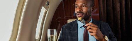 Photo pour Plan panoramique de l'homme afro-américain mangeant en jet privé - image libre de droit