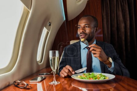 Photo pour Handsome african american man eating salad in private jet - image libre de droit