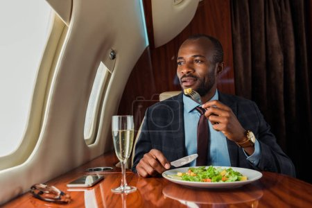 Photo pour Bel homme afro-américain mangeant de la salade en jet privé - image libre de droit