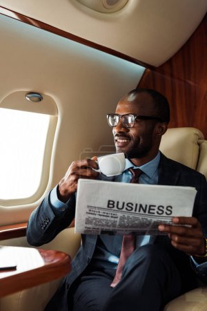 Photo pour Heureux homme d'affaires afro-américain dans des lunettes tenant journal d'affaires et tasse dans un avion privé - image libre de droit
