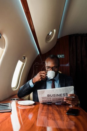 African american businessman in glasses reading business newspaper while drinking coffee in private plane