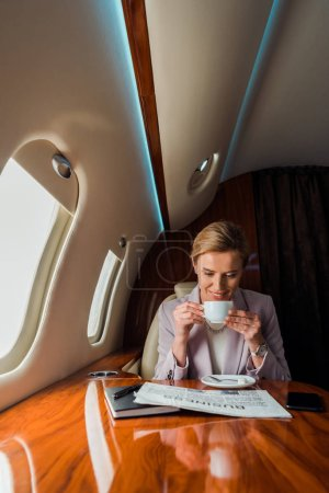 Photo pour Happy businesswoman holding cup while reading business newspaper in private plane - image libre de droit