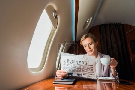 Photo pour Belle femme d'affaires tenant tasse tout en lisant journal d'affaires en avion privé - image libre de droit