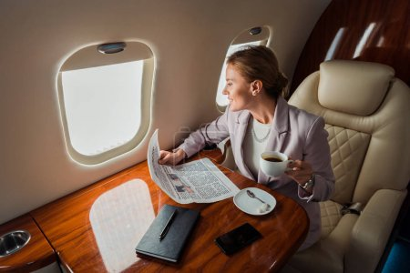 Photo pour Cheerful businesswoman holding cup and business newspaper near smartphone with blank screen in private plane - image libre de droit