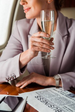 Photo pour Cropped view of businesswoman holding champagne glass in private plane - image libre de droit