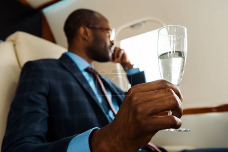 Photo pour Selective focus of african american man holding champagne glass in private plane - image libre de droit