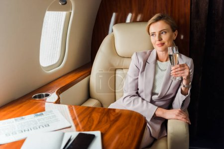 Photo for Happy businesswoman holding champagne glass in private plane - Royalty Free Image