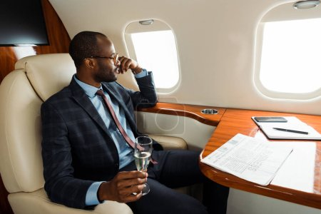 Photo pour Handsome african american man in glasses holding champagne glass in private plane - image libre de droit