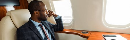 panoramic shot of handsome african american businessman in glasses sitting in private plane