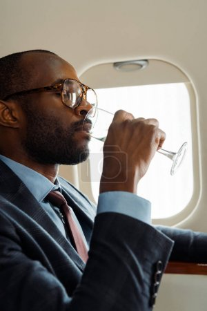 Photo pour Bel homme d'affaires afro-américain à lunettes buvant du champagne en jet privé - image libre de droit