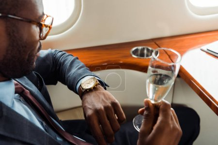 Photo pour Selective focus of african american businessman in suit holding champagne glass in private jet - image libre de droit