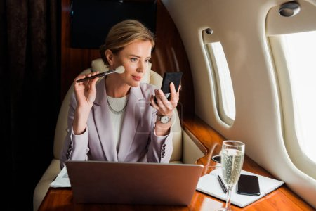 Photo pour Businesswoman applying decorative cosmetics near gadgets and champagne glass in private plane - image libre de droit
