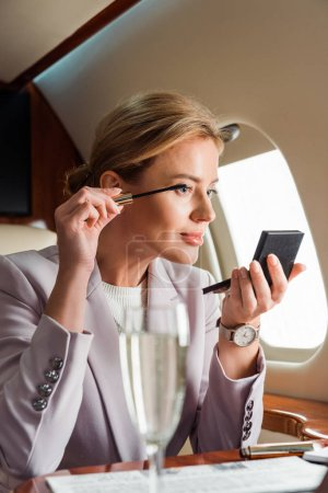 Photo for Selective focus of businesswoman applying mascara in private plane - Royalty Free Image