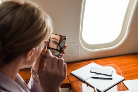 Photo for Selective focus of businesswoman apply mascara in private plane - Royalty Free Image