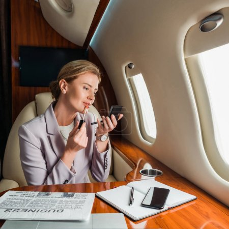 attractive businesswoman applying lip gloss in private jet