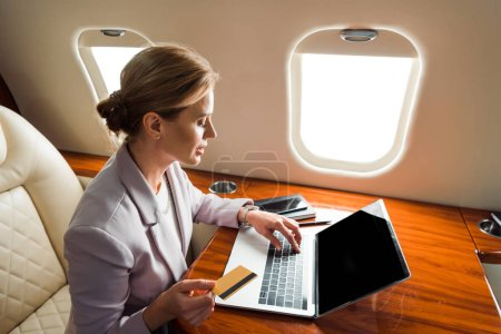 Photo pour Attractive businesswoman using laptop with blank screen and holding credit card in private plane - image libre de droit