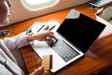 Photo pour Cropped view of businesswoman using laptop with blank screen and holding credit card in private plane - image libre de droit