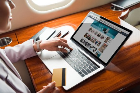 Photo for Cropped view of businesswoman using laptop with amazon website while shopping online in private plane - Royalty Free Image