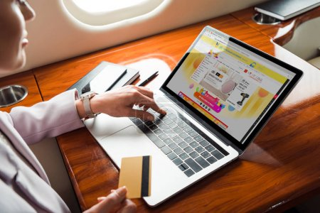 Photo pour Cropped view of businesswoman using laptop with aliexpress website while shopping online in private plane - image libre de droit
