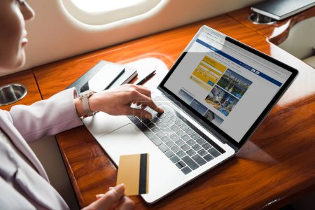 Photo pour Cropped view of businesswoman using laptop with booking website while shopping online in private plane - image libre de droit