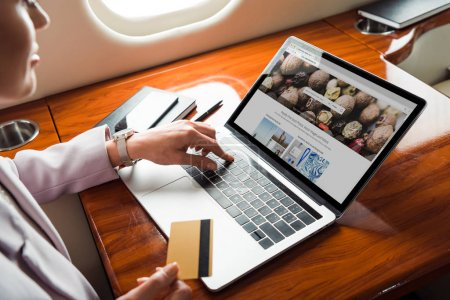 Photo for Cropped view of businesswoman using laptop with depositphotos website while shopping online in private plane - Royalty Free Image