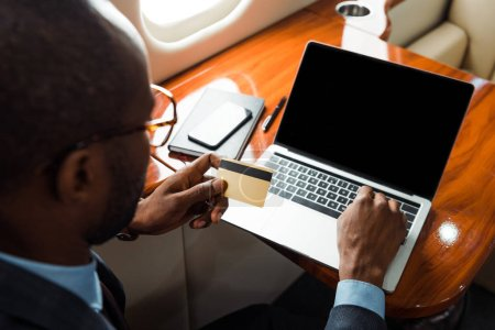 Photo for Selective focus of african american businessman holding credit card near laptop with blank screen in private plane - Royalty Free Image