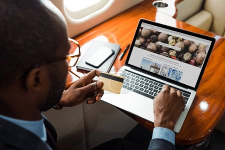 Photo for Selective focus of african american businessman holding credit card near laptop with depositphotos website in private plane - Royalty Free Image