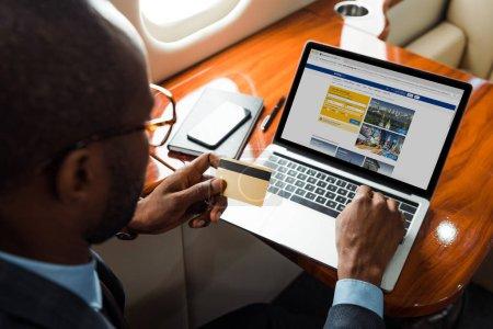 foyer sélectif de l'homme d'affaires afro-américain détenant une carte de crédit près d'un ordinateur portable avec site de réservation en avion privé