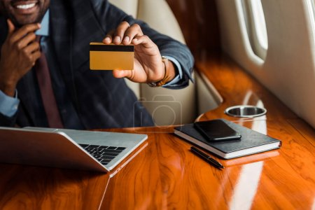 cropped view of african american businessman holding credit card near laptop and smartphone in plane