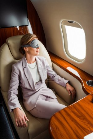 Photo for Businesswoman with sleeping mask sitting near airplane window in private plane - Royalty Free Image