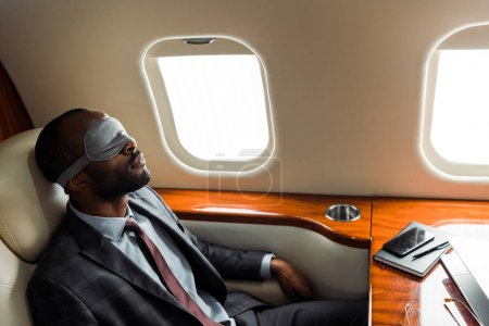 Photo pour African american businessman with sleeping mask sitting near gadgets in private plane - image libre de droit