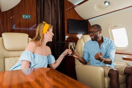 Photo pour Selective focus of happy interracial couple clinking champagne glasses in private plane - image libre de droit