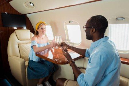 Photo pour Gai interracial couple toasting champagne verres dans privé avion - image libre de droit