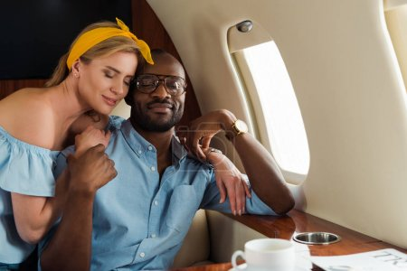 Photo pour Happy woman hugging african american man in private plane - image libre de droit