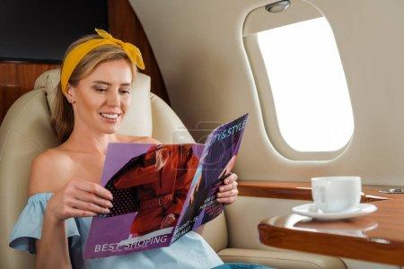 Photo pour Focus sélectif of happy woman reading magazine near cup with drink - image libre de droit