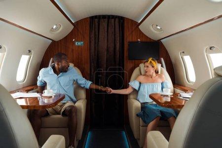 Photo pour Afro-américain effrayé homme et femme tenant la main dans un avion privé - image libre de droit