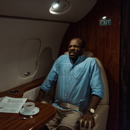 Photo for Stressed african american man with fear of flight sitting in private jet - Royalty Free Image