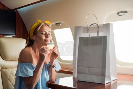 Photo for Happy girl holding credit card near shopping bags in private plane - Royalty Free Image